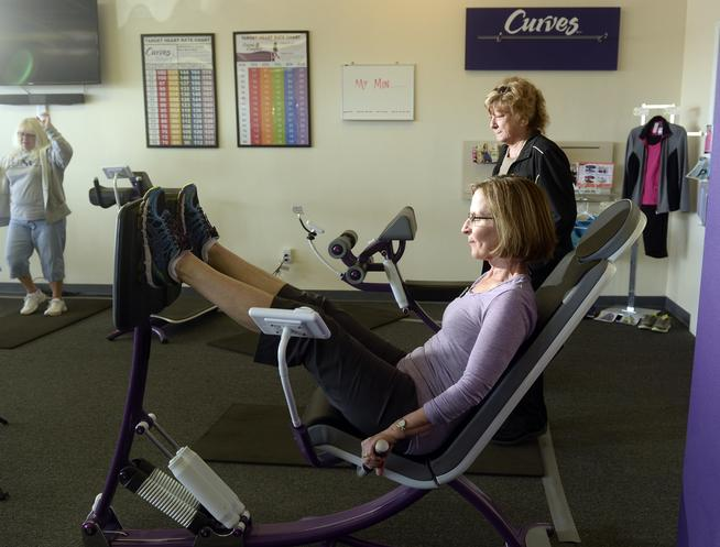 CENTENNIAL, CO - APRIL 15: Fit through menopause at Curves, 7424 S. University Blvd. in Centennial on Wednesday, April 15, 2015 coach Joyce Myers works the leg press machine as she helps customers on the floor of the gym use the hydraulic equipment to maintain strength. (Photo by Cyrus McCrimmon/The Denver Post )